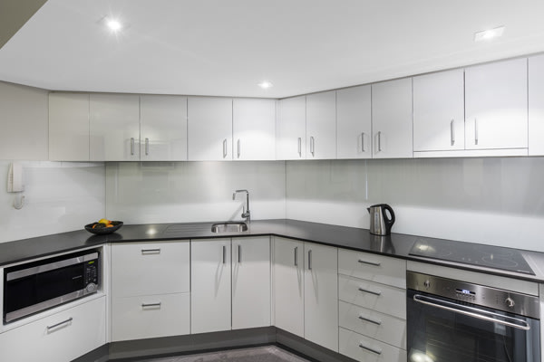 big kitchen area with oven, microwave, kettle and stove top in Oaks Hyde Park Plaza hotel 1 bedroom executive apartment