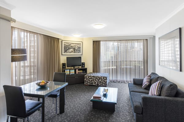 spacious living room with balcony at Oaks Hyde Park Plaza hotel in Sydney central business district