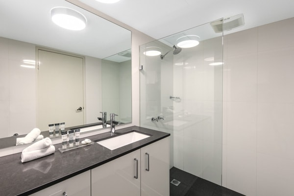 en suite bathroom with shower in 2 bed apartment at Oaks Hyde Park Plaza, Sydney CBD