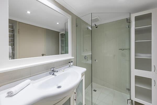 walk in shower in the bathroom of oaks hyde park sydney hotel