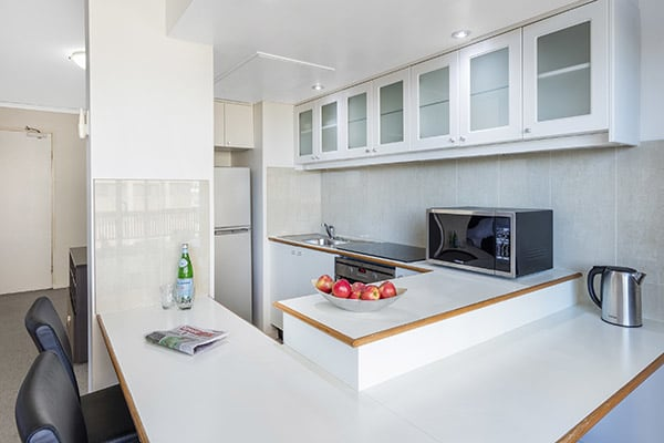 oven, stove top, microwave, cabinets and dining table in the kitchen of oaks hyde park sydney hotel