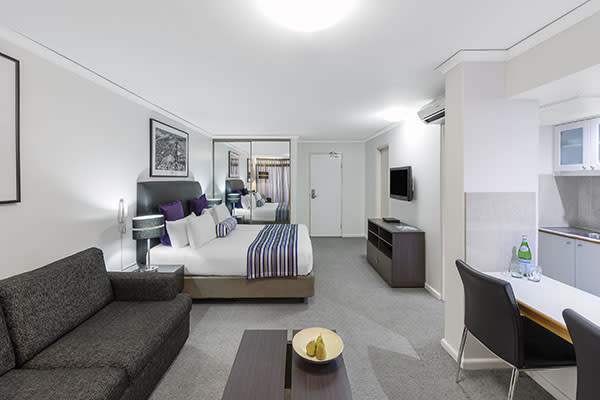 a queen-sized bed, sofa and kitchen in studio executive room of oaks hyde park sydney hotel