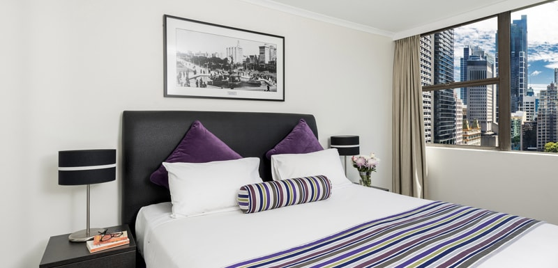 queen size bed in 2 bedroom apartment at Oaks Hyde Park Plaza hotel with views of Sydney skyline