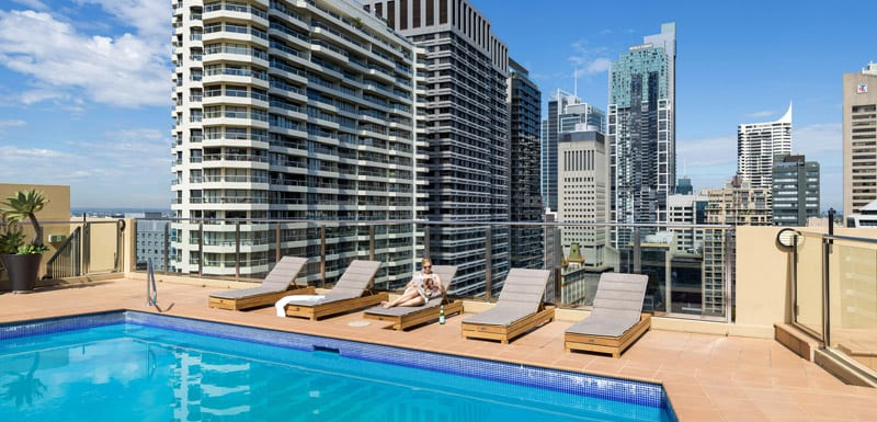 business traveller on sun beds lining outdoor swimming pool at Oaks Hyde Park Plaza in sunshine overlooking Sydney city
