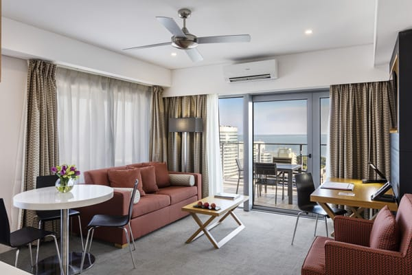 spacious family friendly living room area in 1 bedroom hotel in Darwin with air con and balcony