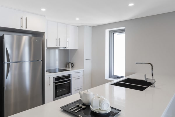 modern kitchen with large refrigerator, air conditioning, oven and kettle at Oaks Elan Darwin hotel