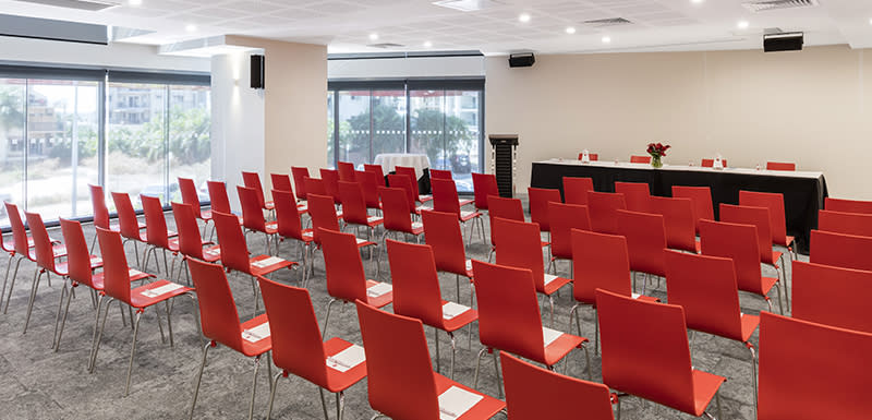 row of red chairs in events room with space for large number of guests at Oaks Elan Darwin hotel