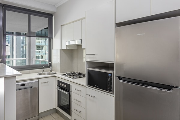 fully equipped kitchen with stove, washing machine, fridge and microwave at 1 Bedroom apartment of Oaks 212 Margaret brisbane hotel