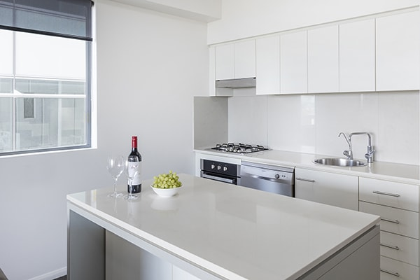 clean and fully-equipped kitchen with stove, washing machine, sink and dining table at oaks 212 margaret 2 bedroom river view brisbane hotel