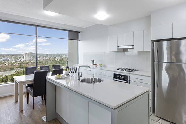 fully equipped kitchen with stove, washing machine, fridge and microwave at oaks 212 margaret 4 bedroom brisbane hotel