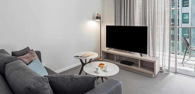 comfy living room with sofa, tables, lamp, connected to balcony at oaks 212 margaret 1 bedroom executive brisbane hotel