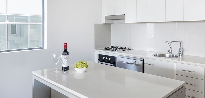 clean and fully-equipped kitchen with stove, washing machine, sink and dining table oaks 212 margaret brisbane hotel