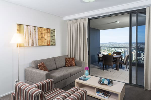 1 bedroom executive apartment living room with air conditioning and balcony with views of Brisbane city centre