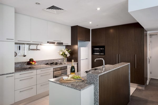 modern kitchen with kettle, oven, microwave and fridge in family friendly 3 bedroom apartment at Oaks Aurora hotel
