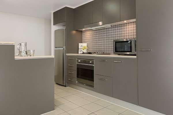fully equipped kitchen with oven, fridge, stove top and microwave at Oaks Brisbane Casino Tower Suites 1 Bedroom Apartment
