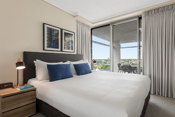 Bedroom connected to a spacious balcony overlooking Brisbane river and southbank at Oaks Brisbane Casino Tower Suites one bedroom executive