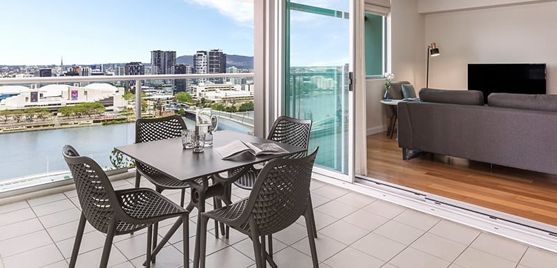 large hotel balcony with furniture and views of Brisbane River walking distance from Treasury Casino