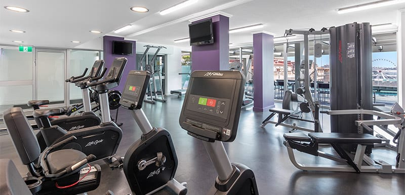 fully equipped hotel gym in Brisbane city with weights, cycling machines and views of Brisbane River