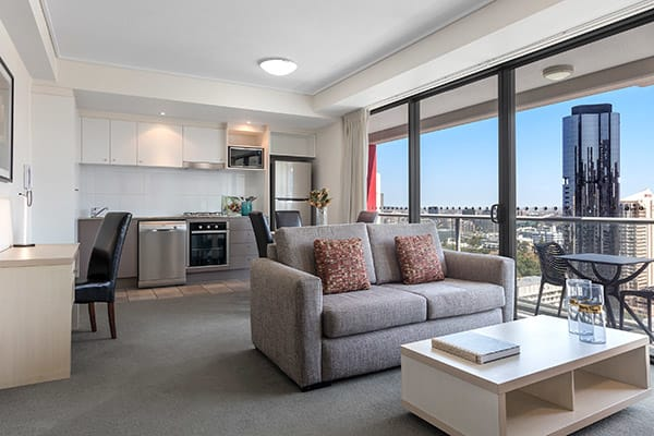 Oaks Brisbane Felix Suites 1 Bed Apartment Living space and open kitchen attached to a spacious balcony with nice city view