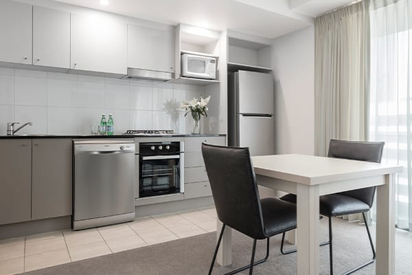 kitchen area in 1 bedroom apartment with large refrigerator and oven at Oaks Felix hotel Brisbane city centre