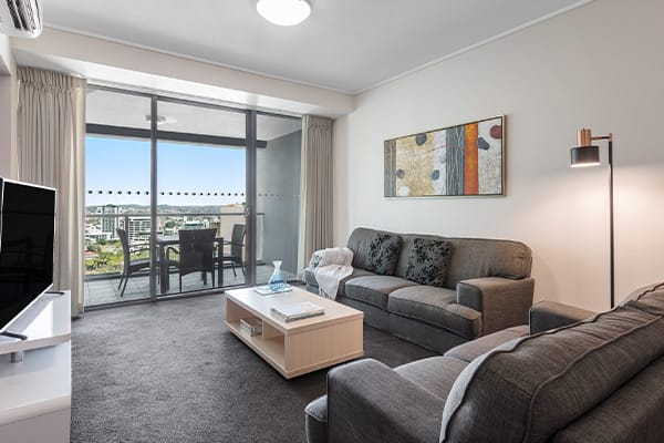 air conditioned living room area with sofa and TV  in 2 bedroom apartment at Oaks Felix hotel in Brisbane CBD