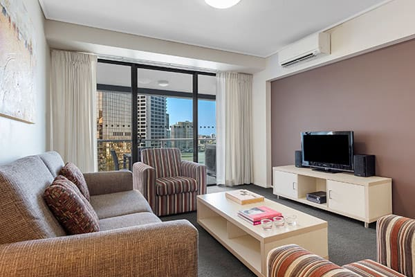 Living room with city view at Oaks Brisbane on Felix Suites 2 Bedroom Story Bridge View