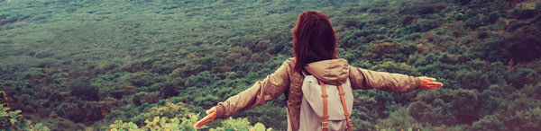 Brisbane traveler with backpack looking at Queensland bushland from top of mountain