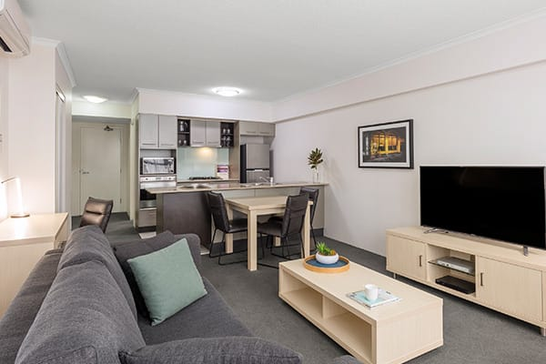 iStay River City two bedroom living in with TV, sofa, dining table