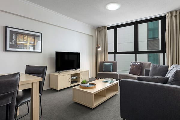 iStay River City two bedroom living in with dining table, TV, sofa,