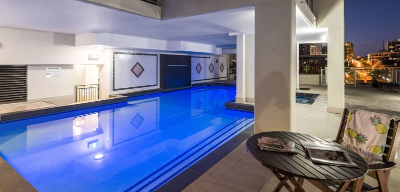 swimming pool at Oaks Lexicon Apartments at night with tables and chairs and views of Brisbane city