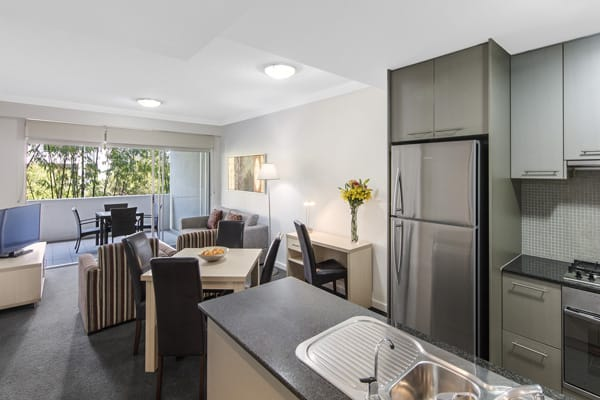 open plan kitchen with full-size refrigerator, microwave, toaster and kettle in 2 bedroom apartment at Oaks Mews hotel in Bowen Hills, Brisbane