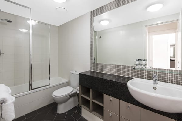 large en suite bathroom with big shower, bathtub, clean towels and toilet in Bowen Hills hotel, Oaks Mews, Brisbane
