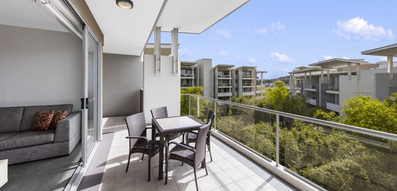 sun shining onto large balcony with tables, chairs and other furniture in Bowen Hills, Brisbane