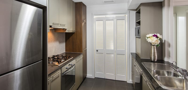 kitchen with modern appliances including full-size fridge, oven, sink and microwave at Oaks Mews hotel apartments in Bowen Hills