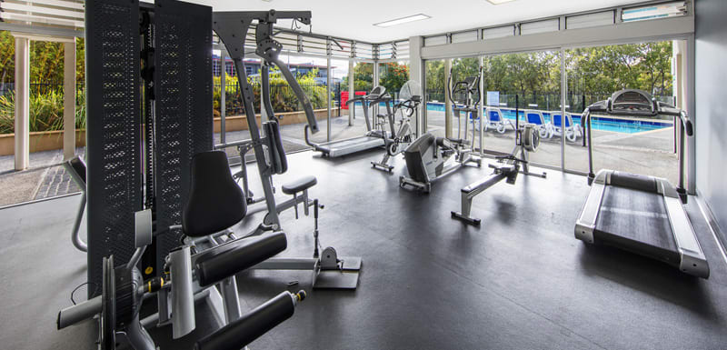 hotel guest using treadmill in fully equipped gym in Bowen Hills with swimming pool in Brisbane