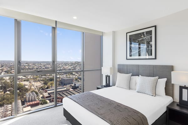comfortable queen size bed in 1 bedroom apartment with large windows and panoramic views of Brisbane