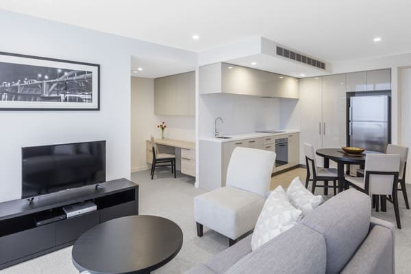 large living room area with flat screen television in air conditioned 1 bedroom executive apartment at The Milton Brisbane hotel