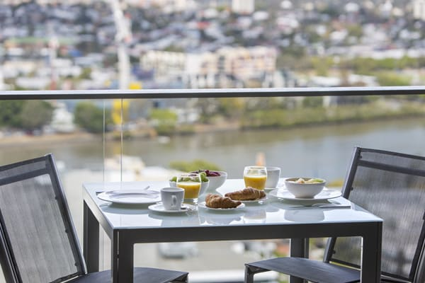large balcony of 1 bedroom apartment with fresh fruit and tea cups on table and views of Brisbane River in background