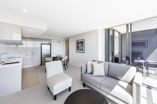 modern couches and appliances in air conditioned 1 bedroom apartment opposite Suncorp rugby Stadium