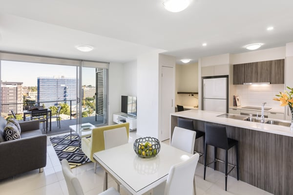 open plan living room and kitchen with modern appliances and comfortable furniture at Oaks Woolloongabba hotel