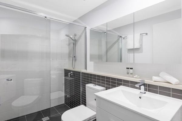 big en suite bathroom with adjustable shower head and toilet in 2 bedroom apartment at Oaks Woolloongabba hotel