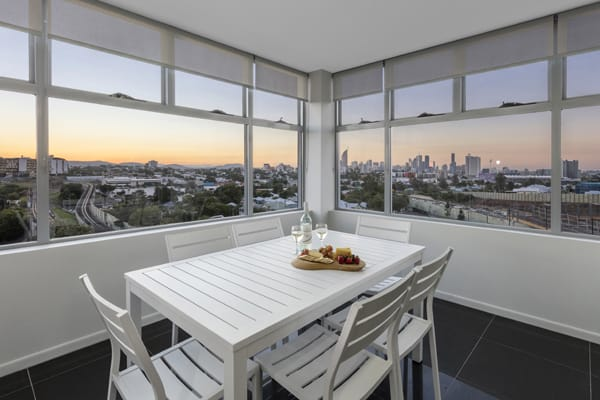 2 bedroom apartment balcony with furniture and views of Brisbane at sunset from Oaks Woolloongabba hotel