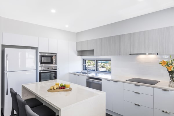 Oaks Woolloongabba hotel kitchen with large refrigerator and microwave on OKeefe St in Brisbane