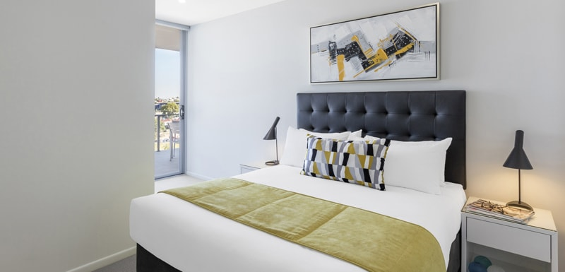 queen size bed with side tables and sliding glass doors leading out to balcony with views of Woolloongabba and Brisbane