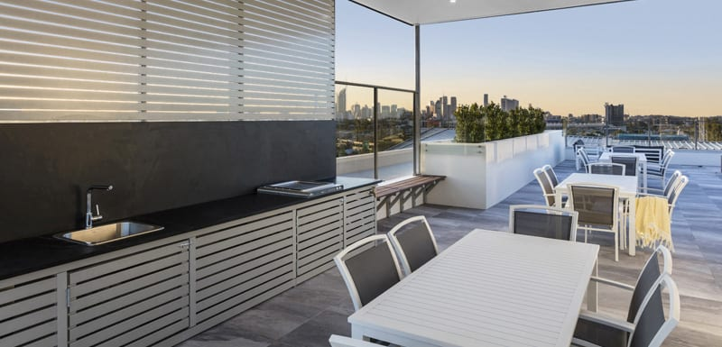 outdoor BBQ area at Oaks Woolloongabba hotel with views of Brisbane city in distance at sunset