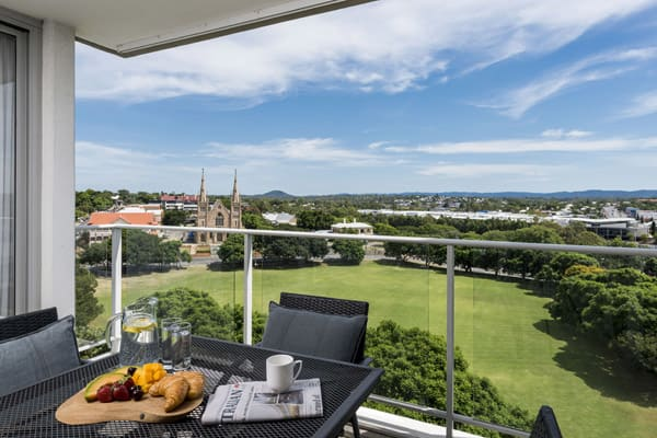 hotel balcony with tables and chairs and beautiful of green park in Ipswich, Queensland