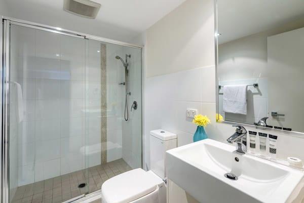 clean en suite bathroom with large shower and toilet at Oaks Aspire hotel Ipswich, Queensland