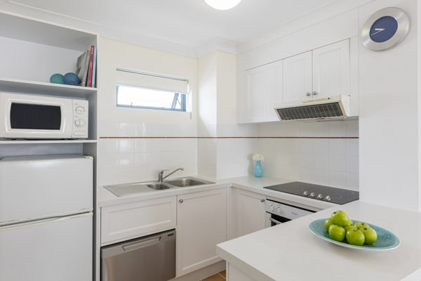 modern kitchen in 1 bedroom apartment with big fridge, microwave and stove top oven for hotel guests to use