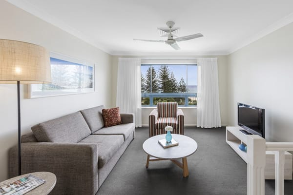 spacious air conditioned living room with TV, Foxtel, comfortable couches and ceiling fan at Oaks Calypso Plaza resort in Coolangatta, Australia