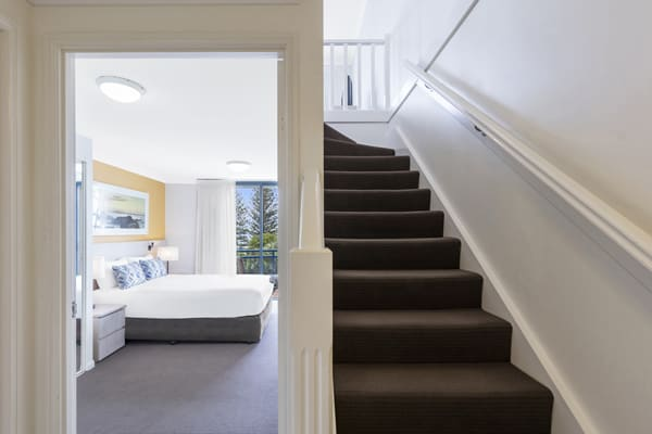 staircase leading to second level of 1 bedroom executive apartment at Oaks Calypso Plaza resort in Coolangatta, Australia